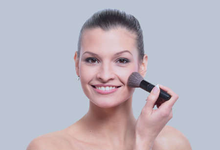 Woman applying dry cosmetic tonal foundation on the face using m