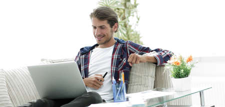 happy young man working with laptop from home.