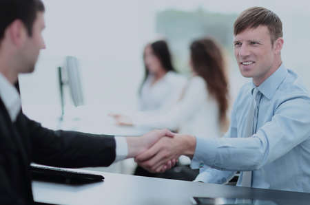 Business handshake. Two business people shaking hands in office. Stock Photo
