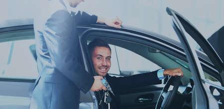 jeune homme choisissant voiture au salon avec aide de consultant