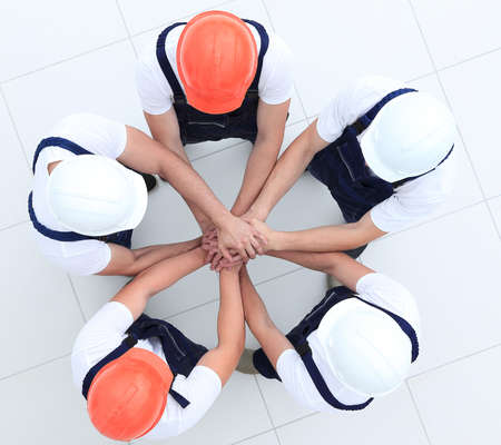 group of construction workers with hands clasped together Stock Photo
