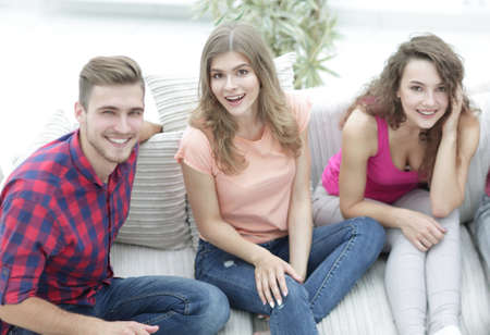 group of cheerful friends watching videos, sitting on the couch