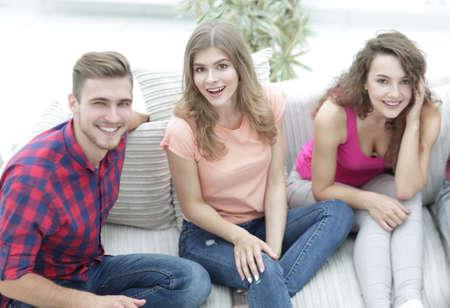 groupe d'amis gais regarder des vidéos, assis sur le canapé