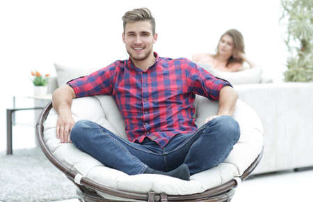 modern young man sitting in a big round chair on blurred background