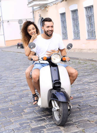 Full length side view of happy couple riding on retro motorbike Stock Photo