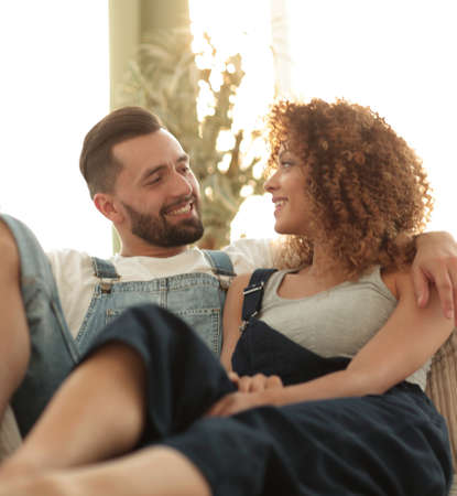 Young couple in work clothes sitting on couch