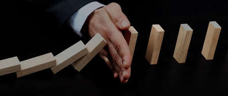 male hand placing wooden block on a tower. planing and strategy concept