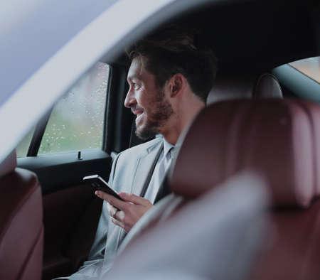 186e165336 #92657894 - Feliz joven empresario mediante teléfono móvil en el asiento  trasero del coche