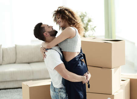 Hugging couple, against the background of boxes Stock Photo