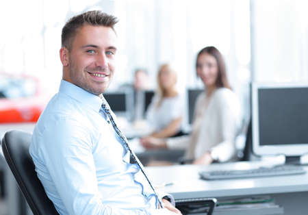 successful employee sitting behind a Desk and looking at the camera. Stock Photo