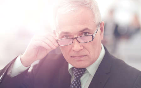 Portrait of mature businessman with  colleagues interacting on b Stock Photo