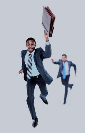 Happy afroamerican man running with a briefcase in hand. in the background- his colleague, trying to catch up him.