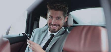 c517ffdef6 #93068113 - Feliz joven hombre de negocios usando el teléfono móvil en el  asiento trasero del coche