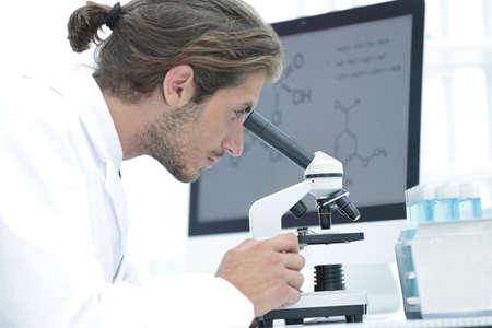 senior lab technician using microscope in laboratory