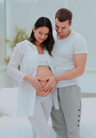 man and woman illustrayte the heart on her baby bump by hands. Banque d'images