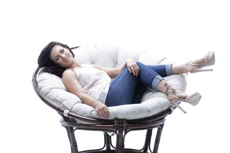 modern young woman relaxing in a round cozy soft chair. Banque d'images