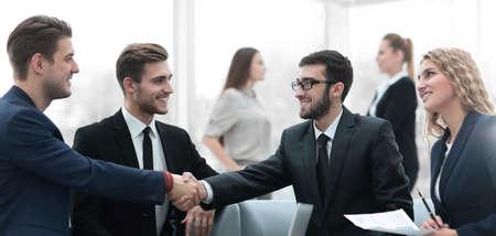Partners sluiten deal en handschudden in aanwezigheid van teamleden Stockfoto