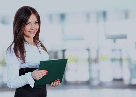 Positieve bedrijfsvrouw die over witte achtergrond glimlacht.
