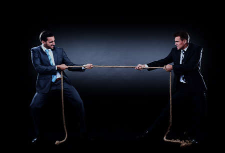 Two business men pulling rope in a competition, isolated on white background. Foto de archivo