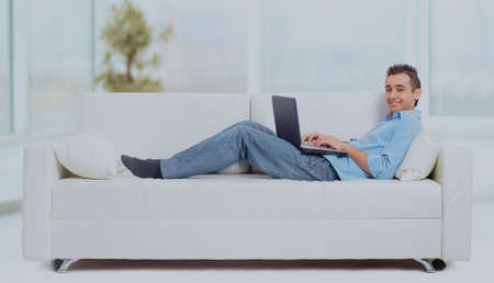 a man lying on the sofa working on the computer. Stock Photo