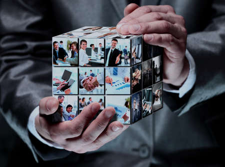 man holding abstract cube with business images