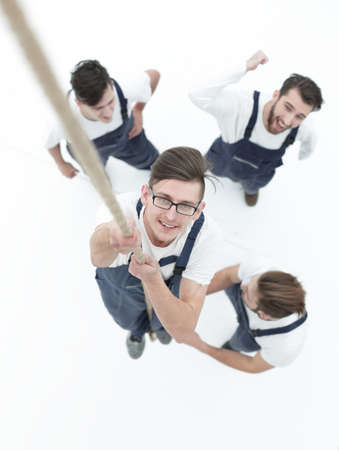 team, helping the leader to climb up the rope. Stock Photo