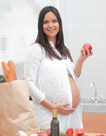 young pregnant woman holding an Apple,standing in the kitchen