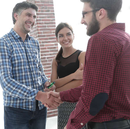 Happy young business people shaking hand at creative office Stock Photo