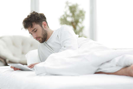 man lying on bed and using digital tablet in bedroom