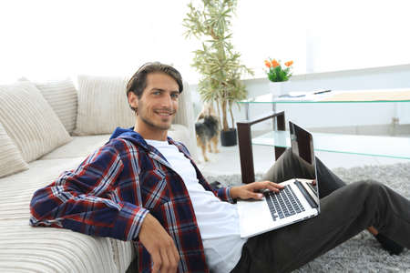 charming young man with laptop sitting in modern living room