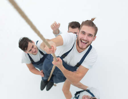 view from the top.smiling engineer ,climbing up the rope Stock Photo