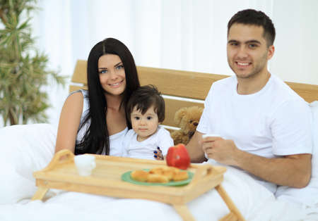 Family having breakfast in bed at home Stock Photo