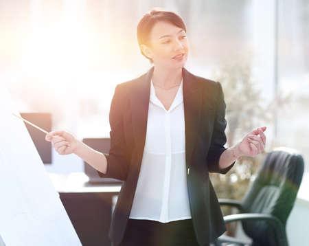 donna di affari che mostra le informazioni di una squadra di affari sulla lavagna a fogli mobili