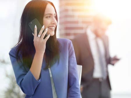 Attractive brunette businesswoman talking on mobile phone with c
