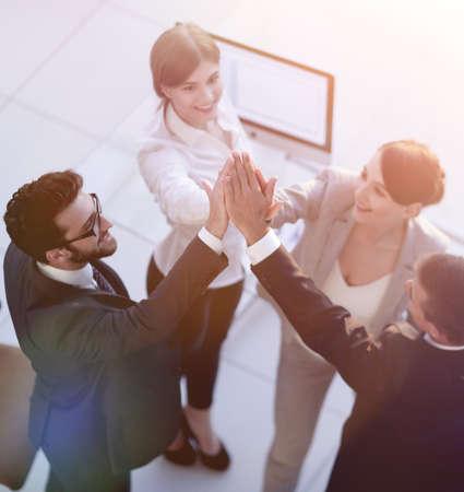 successful business team giving each other a high-five, standing Standard-Bild