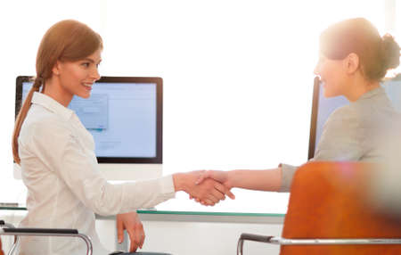 background image. business woman stretches out hand for a handshake. Standard-Bild