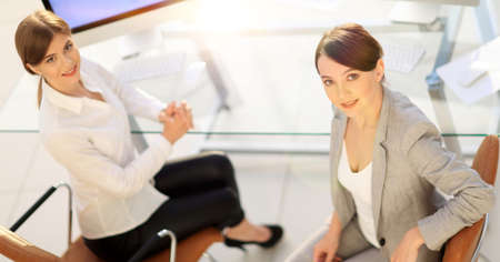 view from the top rear.business woman with a colleague sitting at a Desk