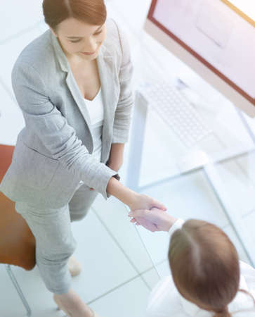 view from the top.business woman shaking hands with employee