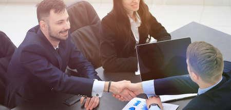 handshake financial partners sitting at the table Standard-Bild