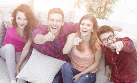 group of laughing friends sitting on sofa and showing forefinger Standard-Bild