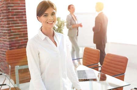 young woman assistant standing near desktop. Standard-Bild