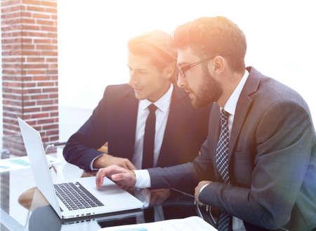 Two business men working on a laptop Standard-Bild