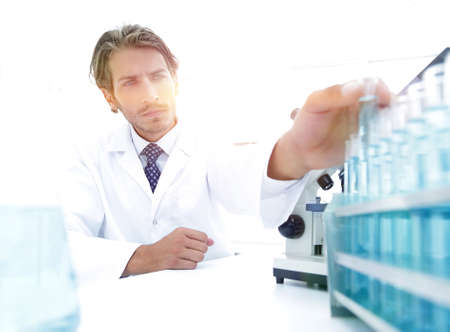 Chemist looking at test-tubes with blue liquids Stock Photo
