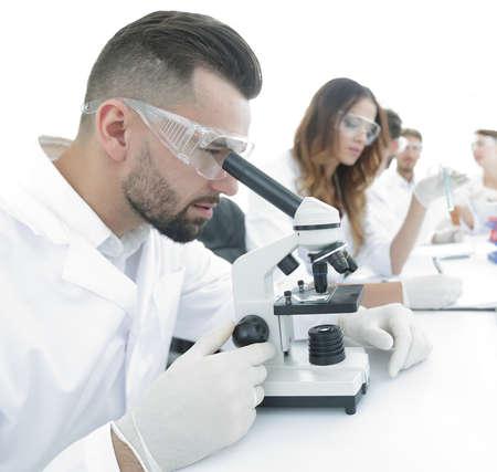 male lab technician looks at the sample under a microscope Foto de archivo