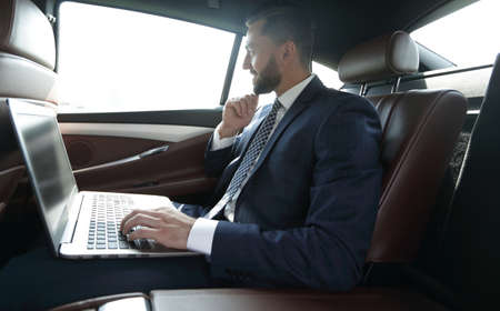 Businessman typing text on laptop while sitting in car