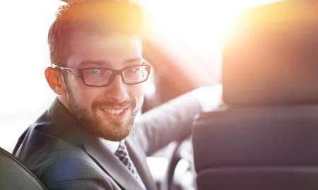 man in formalwear sitting in car