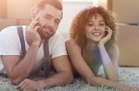 Portrait of a married couple lying on the floor after moving Stock Photo