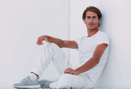 sad young man sitting beside a white wall