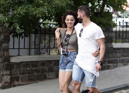 Cheerful young couple walking on urban street 스톡 콘텐츠