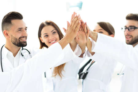 group of doctors giving each other a high five. Stock Photo